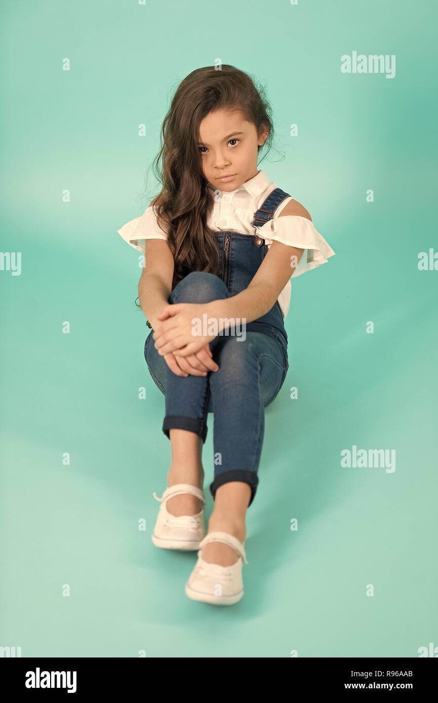 Bambina con lunghi brunette capelli in jeans nel complesso su sfondo blu. Moda, stile concetto. Bellezza, look, acconciatura. Infanzia, preteen, gioventù, pastello incalzanti Immagini Stock