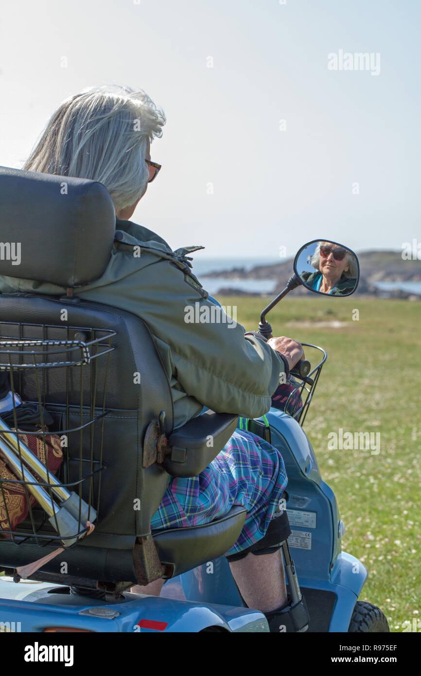 Disabilitato. PHysically compromessa, OAP. Una donna anziana, la guida a quattro ruote di veicolo elettrico dando piacevole indipendenza e accesso alla campagna the, ambiente rurale. Iona, nella costa occidentale della Scozia. Immagini Stock