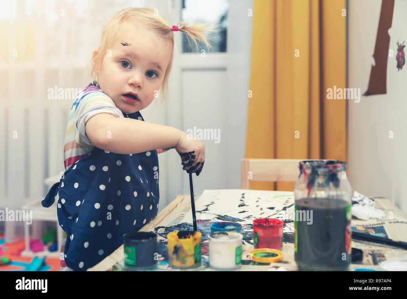 Bambina con pittura a tempera i colori a casa Immagini Stock