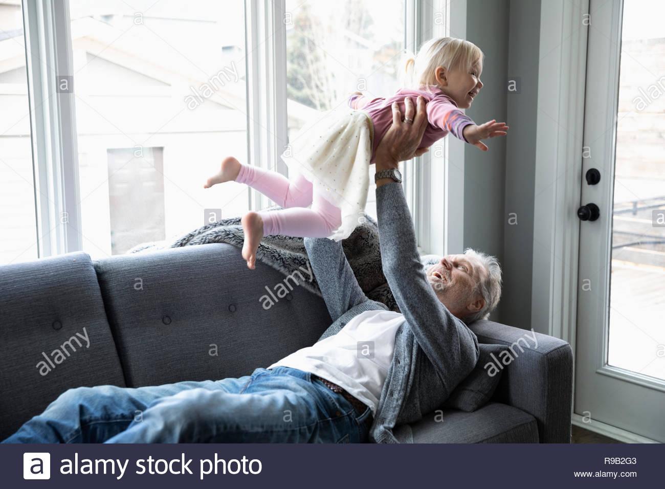 Giocoso nonno toddler sollevamento nipote overhead sul divano Immagini Stock