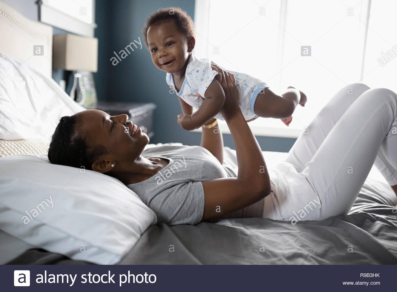 Giocoso azienda madre figlio bambino sul letto Immagini Stock