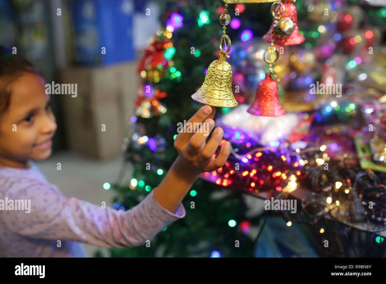 Ragazza vede lo shopping di Natale in un negozio prima delle vacanze di Natale e Capodanno a Dhaka, nel Bangladesh sul dicembre 20, 2018. Immagini Stock