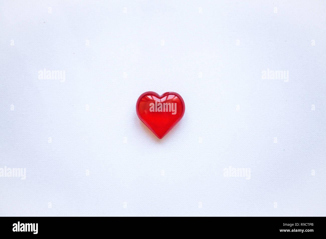 Cuore rosso su sfondo bianco. Concetto per il giorno di San Valentino o il giorno della donna o il tema della salute, la vita, la donazione e la guida in linea di . In stile minimal. Foto Stock