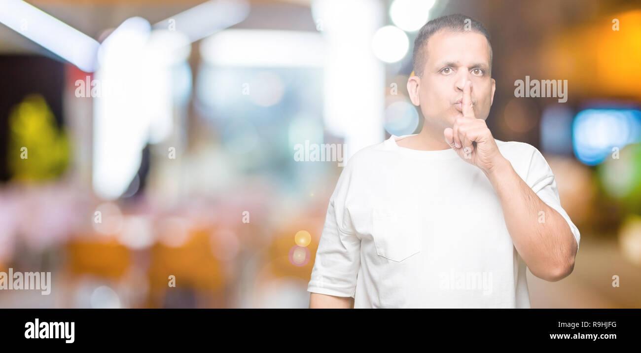 La mezza età uomo arabo wearig t-shirt bianco su sfondo isolata chiedendo  di essere 258af4f69ae4