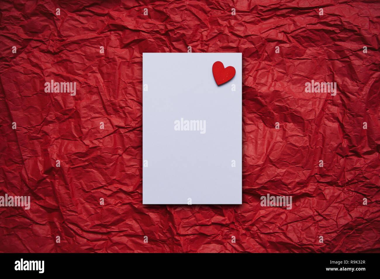 Vuoto Bianco Foglio Di Carta Con Un Cuore Rosso Su Sfondo Rosso Foto