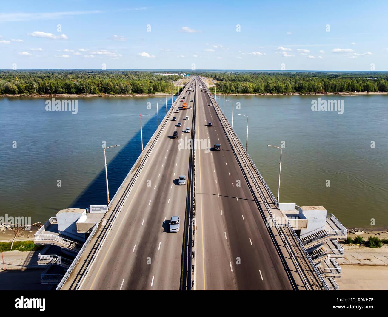 Vista la ben costruite città ponte che attraversa il fiume. City River cancelli. Trasportation attraverso il fiume alla foresta e orizzonte sfondo. Vehicula Immagini Stock