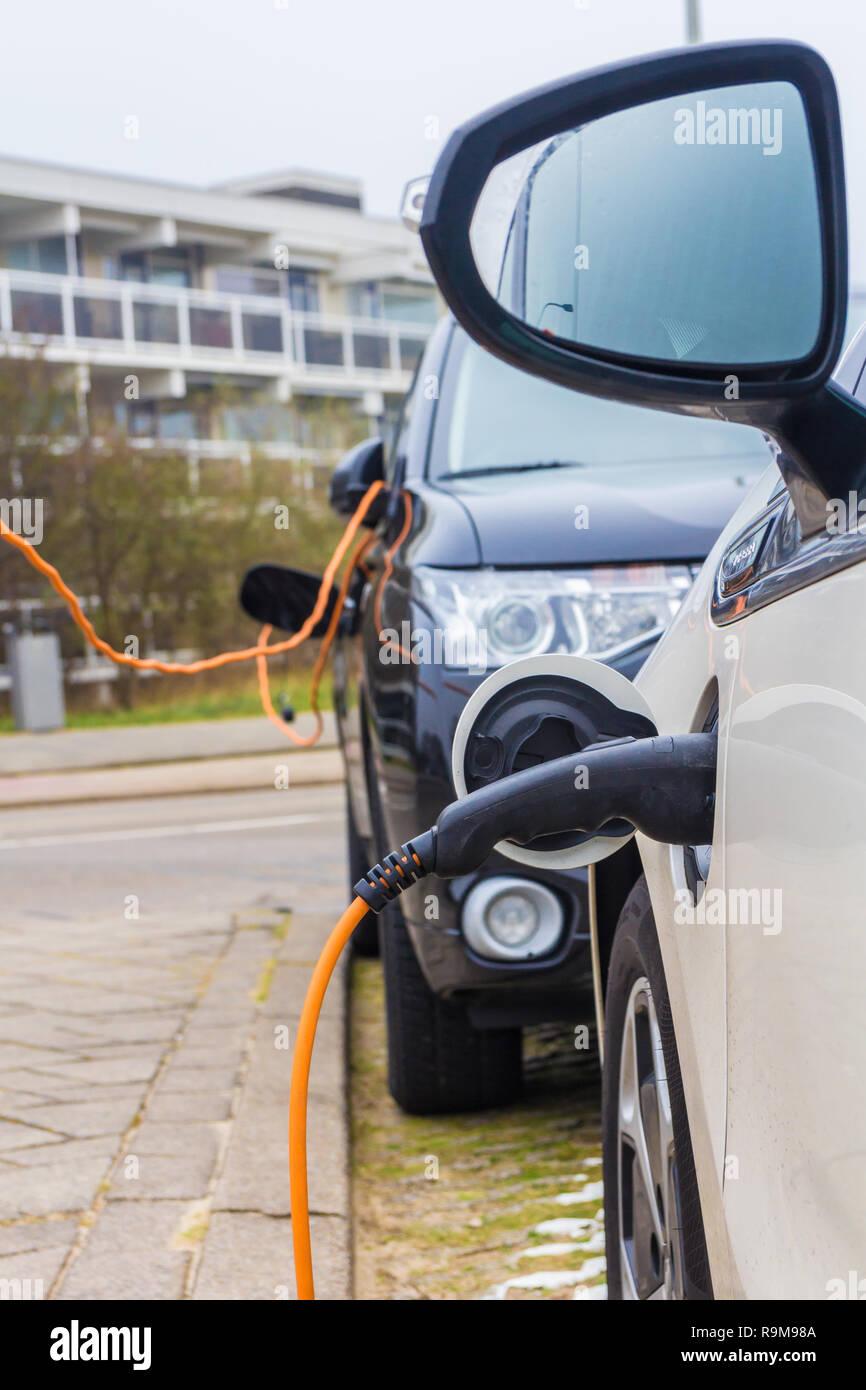 Kijkduin, l'Aia, Paesi Bassi - 13 Gennaio 2018: hybrid auto elettriche ricarica con spina elettrica nella stazione di alimentazione Immagini Stock