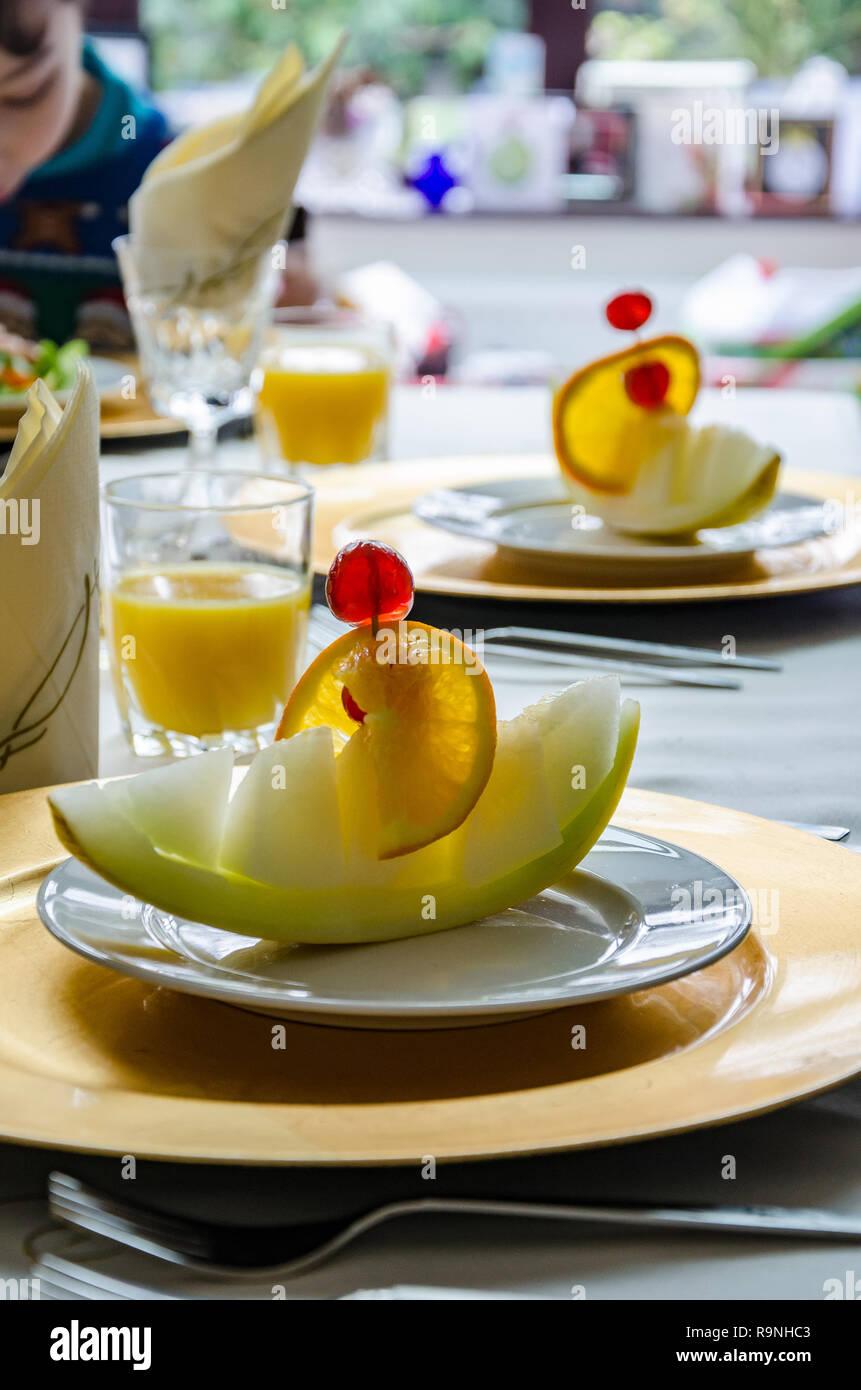 Una fetta di melone presentata come una barca di melone su una piastra su un tavolo da pranzo pronto a mangiare come un primo corso. Immagini Stock
