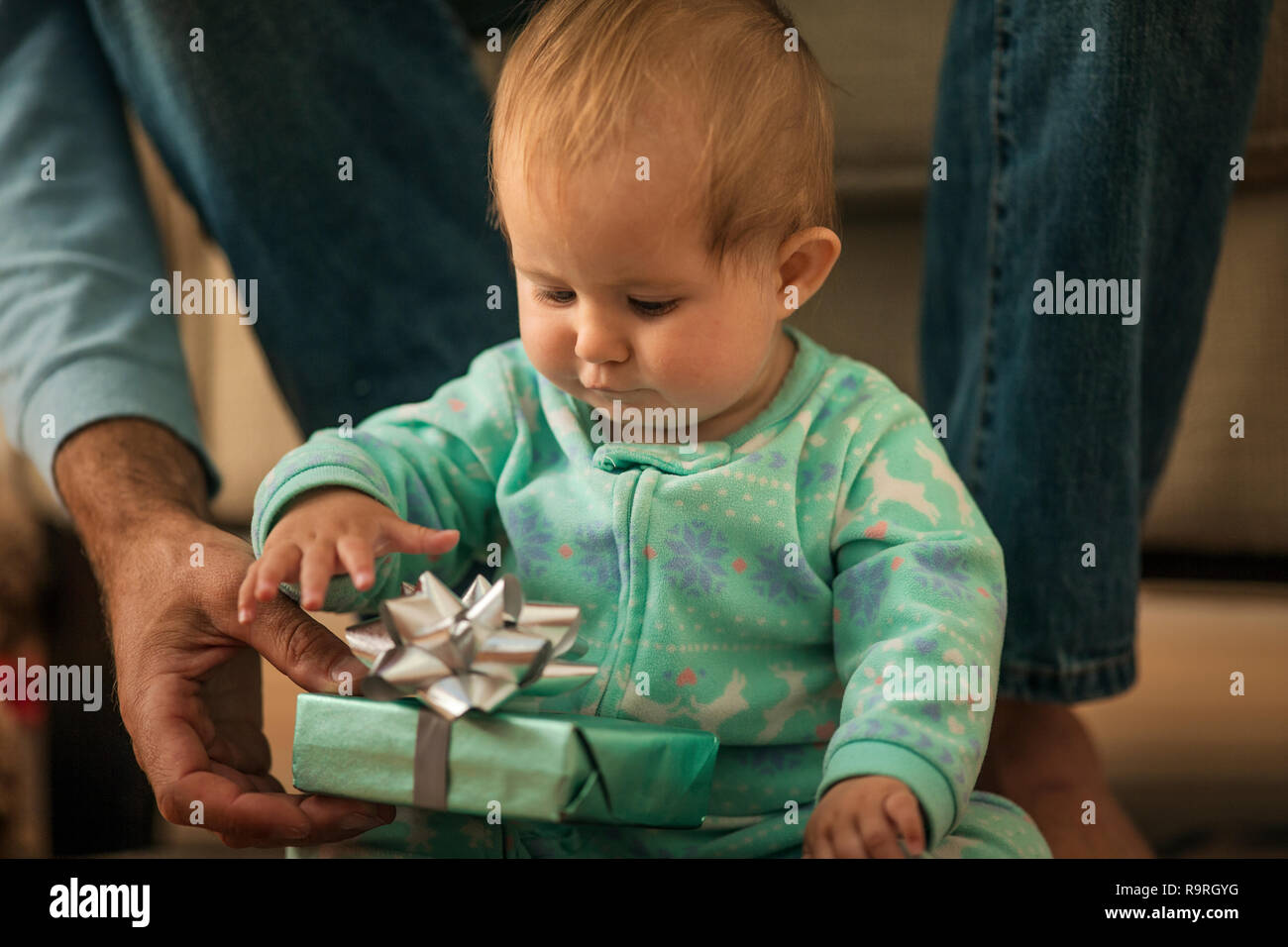 Baby girl apertura di un presente da suo padre. Immagini Stock