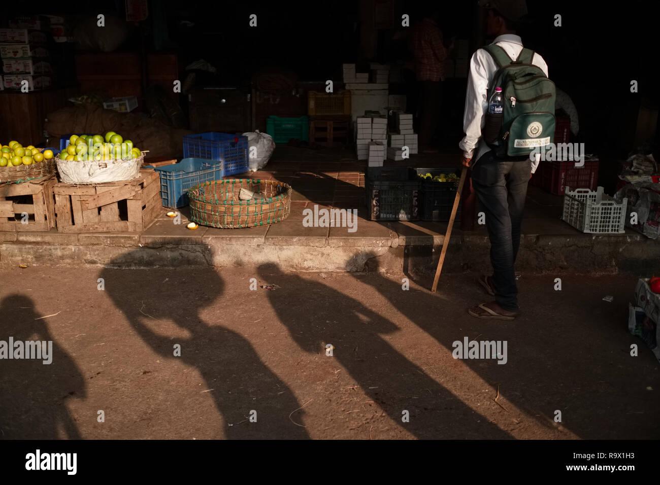 Ombre di facchini e il fotografo che cade a Crawford mercato o Mahatma Jyotiba Phule Market, un mercato di frutta e verdura, Mumbai, India Immagini Stock