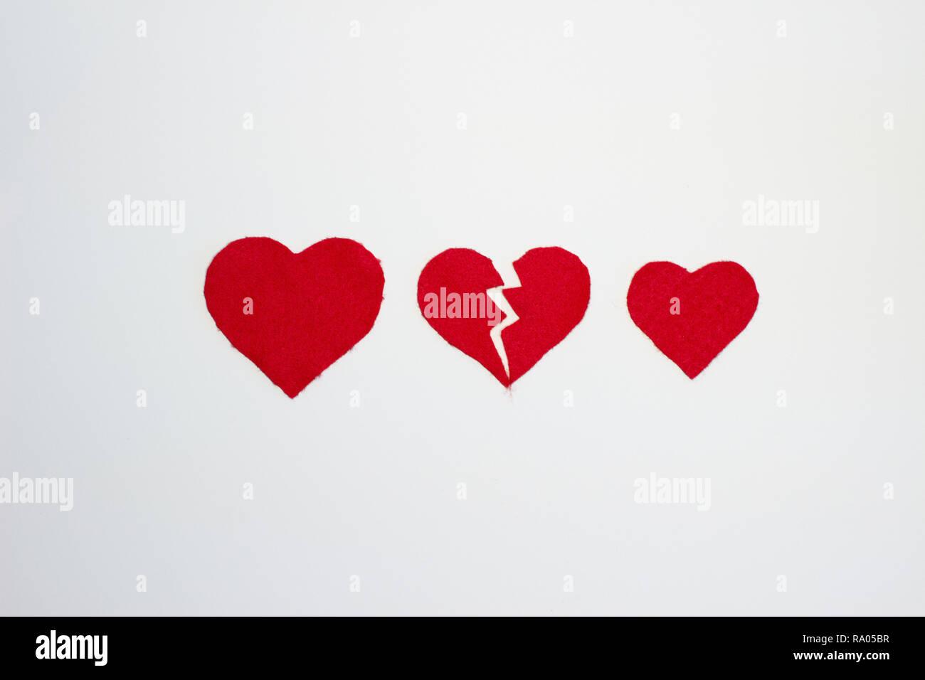 Heartbreak e amore rappresentato dal feltro rosso cuori Immagini Stock