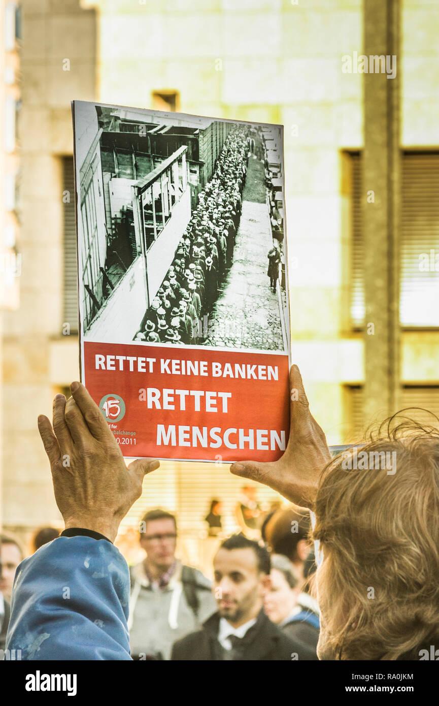 Giovane uomo tenendo un poster con un testo che recita: _ non salvare le banche, salvare gli esseri umani _, la dimostrazione contro la speculazione finanziaria Immagini Stock
