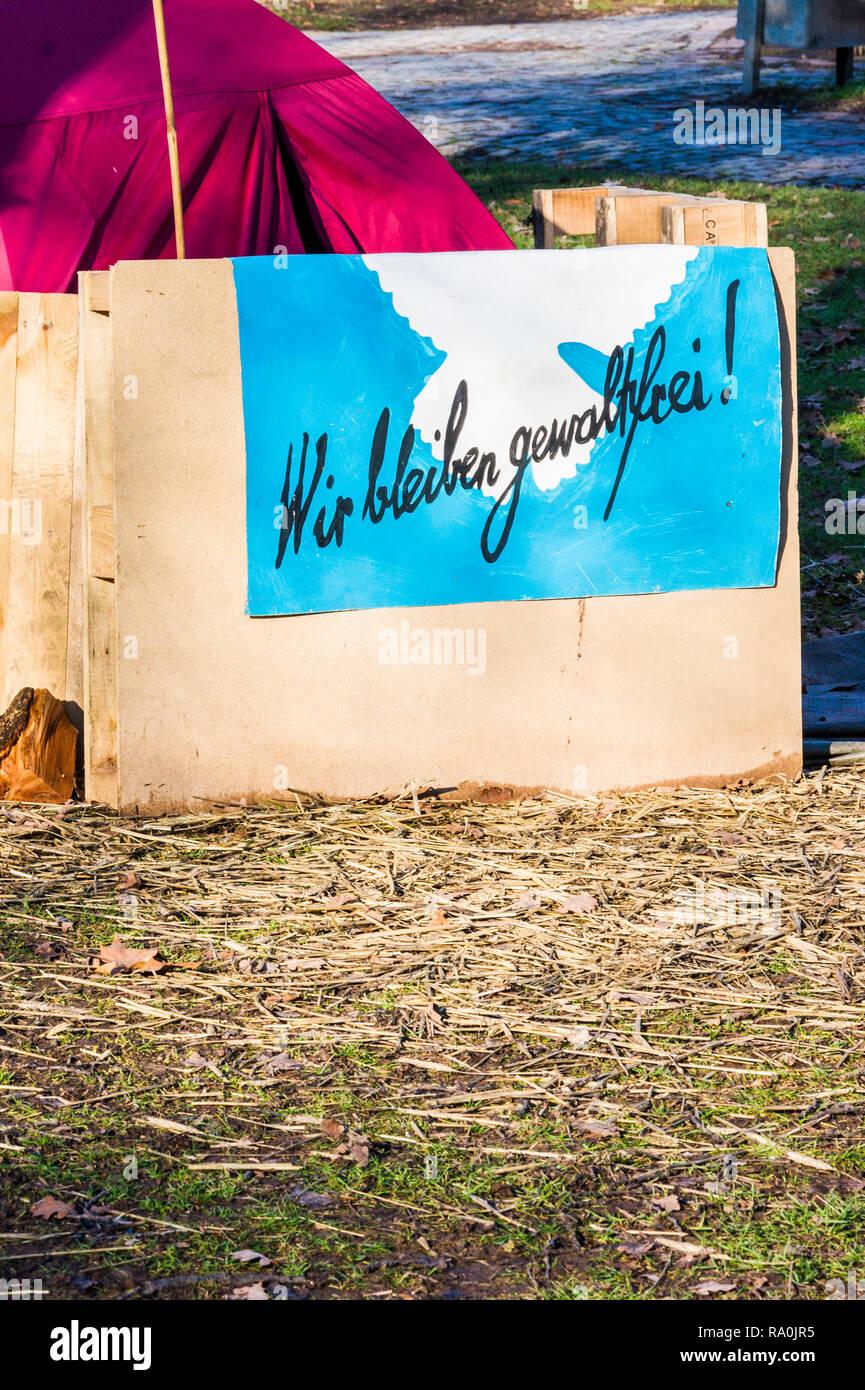 """Poster, testo recita: """"wir bleiben gewaltfrei'/andremo a stare non-violento"""" Immagini Stock"""