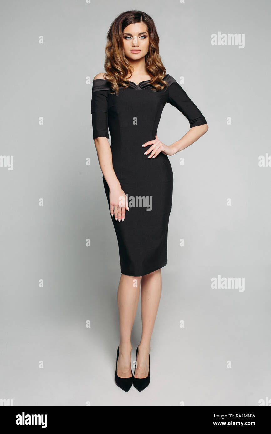 39be6de2a81e Ritratto in studio di bella donna elegante con brunette capelli ondulati in  nero abito classico con