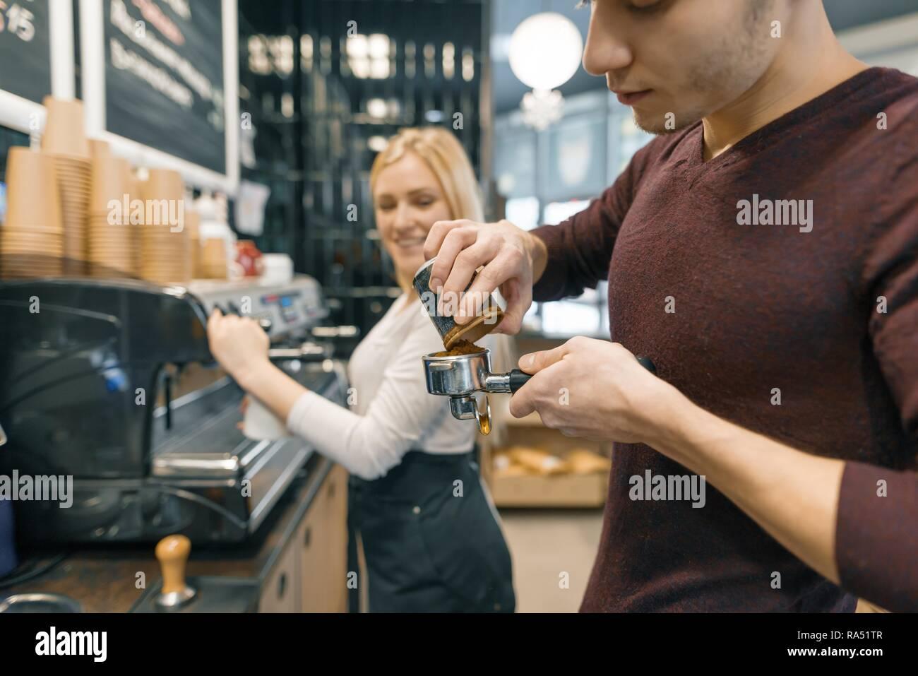 Barista uomo e donna fare il caffè, coppia di giovani che lavorano nella caffetteria. Foto Stock