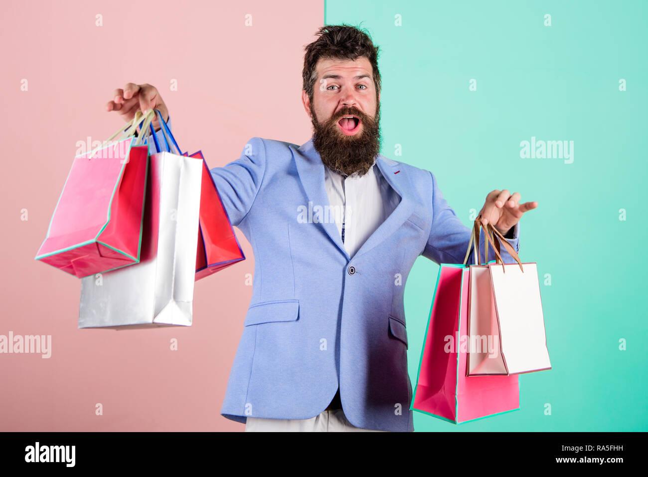 Acquistare regali in anticipo. Godetevi lo shopping venerdì nero. Hipster shopping con lo sconto. Uomo Barbuto hipster imprenditore abito formale di trasportare la carta delle borse per lo shopping. Acquistare regali per tutti. Pronto per le vacanze. Immagini Stock