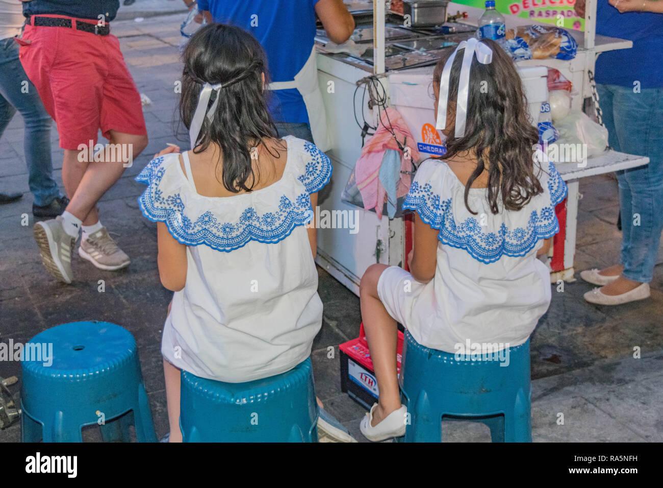 Due giovani ragazze in identici abiti di colore bianco con ricamo blu, seduti a un cibo in stallo sulla strada, in Oaxaca, Messico Immagini Stock