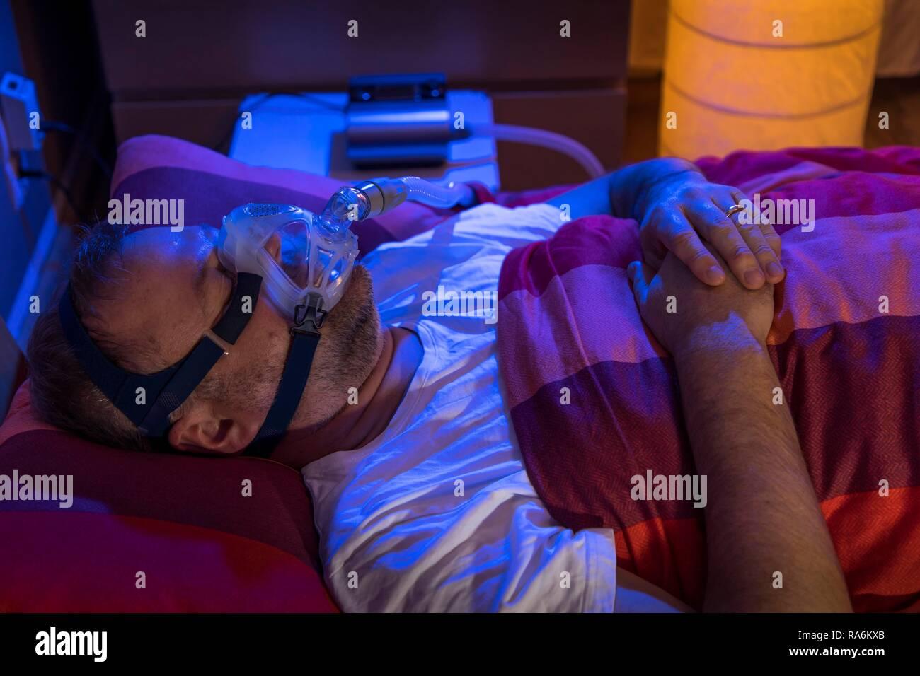 Uomo con sindrome da apnea nel sonno, indossa una maschera CPAP durante il sonno, una maschera per la respirazione, che spinge aria nelle vie respiratorie dovute Immagini Stock