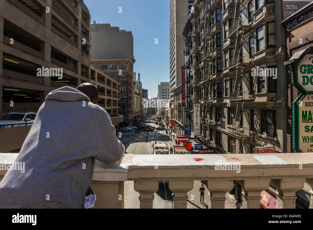 Un afro-americano con una felpa bianca si appoggia su un mancorrente a Bush Street di San Francisco, California, Stati Uniti d'America Immagini Stock