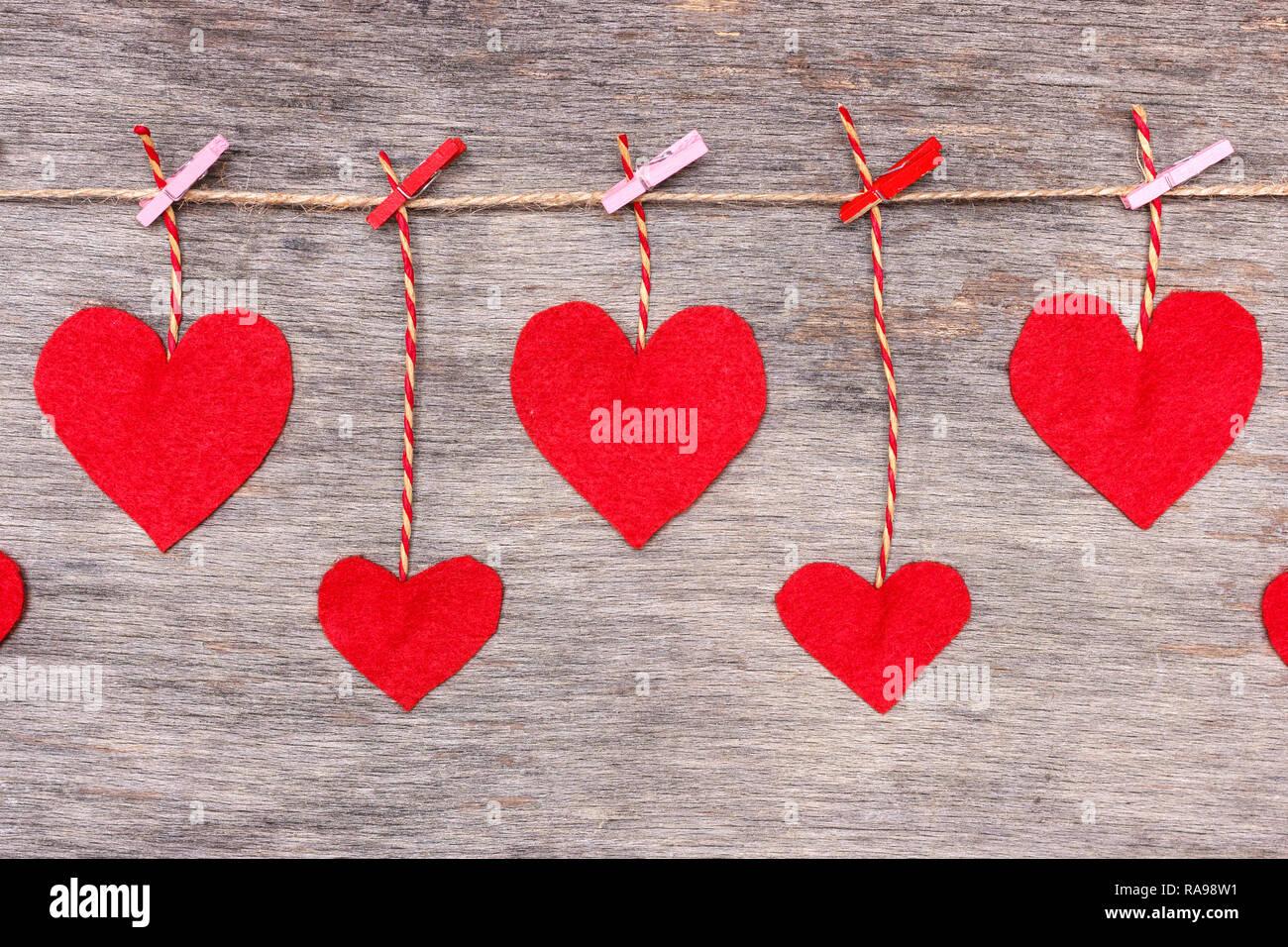 Rosso di San Valentino di cuori sul cordoncino naturale e spine di rosa appeso sul rustico sfondo texture, spazio di copia Foto Stock