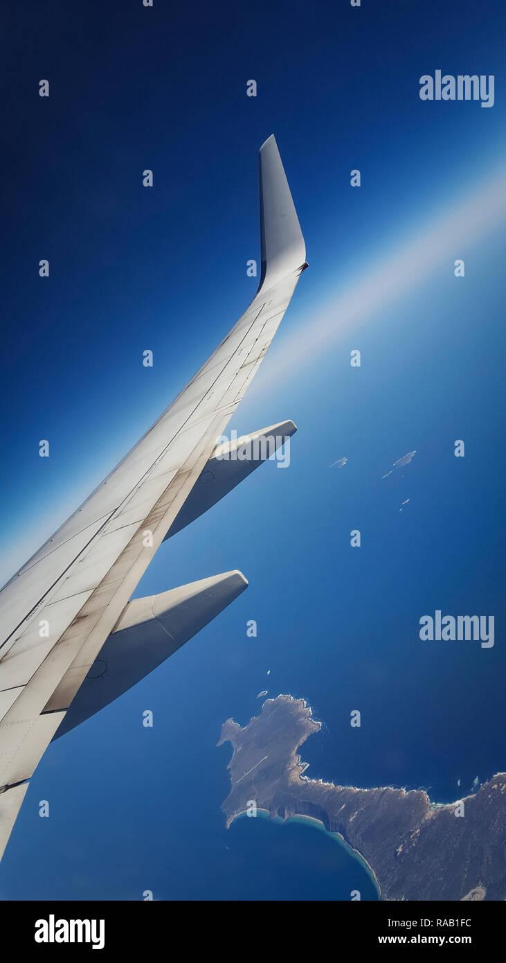 Visualizza la finestra di aereo con ala e la curvatura della terra in background Immagini Stock