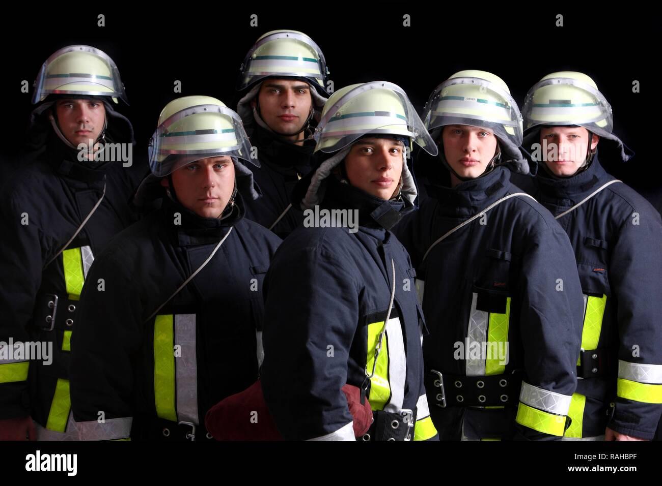 I vigili del fuoco che indossano le loro uniformi per una risposta, abbigliamento protettivo realizzato in Nomex, un casco con una visiera, professional Foto Stock