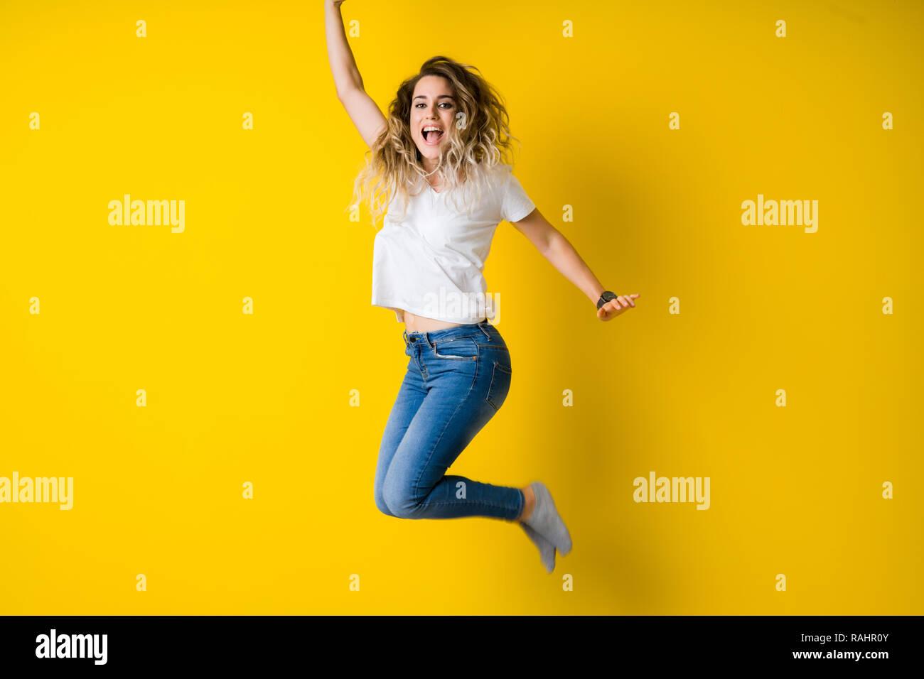 808e9e597a82 Giovane e bella donna bionda jumping felice ed entusiasta isolato su sfondo  giallo Immagini Stock