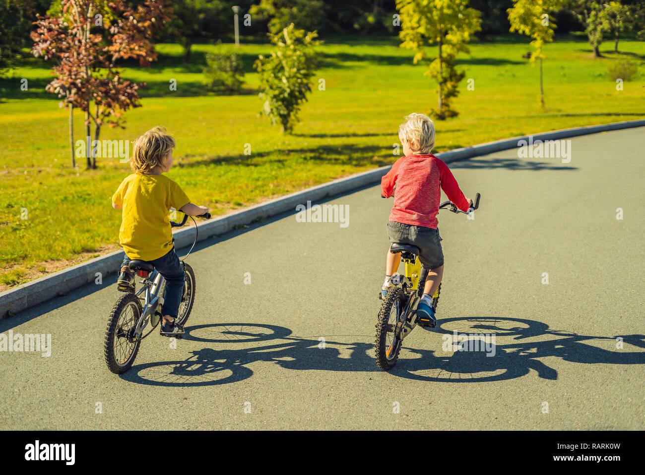 Due ragazzi felice in bicicletta nel parco Foto Stock