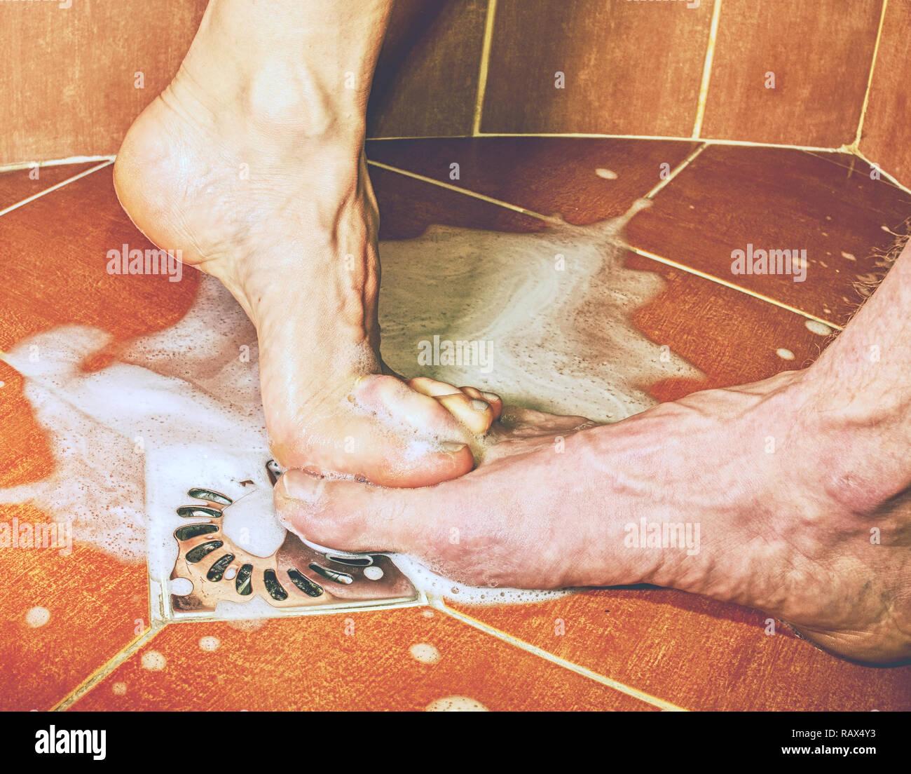 Gli amanti degli adulti giocando con il piede nella sala da bagno con doccia. Bel momento di insieme vivere giovane Foto Stock