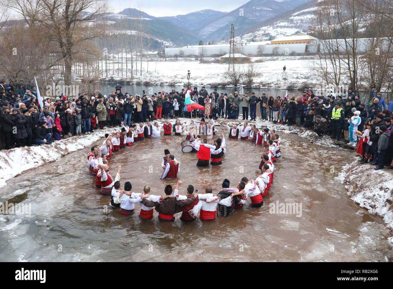 """Zverino, Bulgaria. 6 gennaio 2019: le persone a svolgere la nazionale di danza """"Horo' nelle gelide acque del fiume Iskar nel villaggio di Zverino, durante le celebrazioni del giorno dell'Epifania il 6 gennaio 2019. Credito: GeorgiD/Alamy Live News Immagini Stock"""