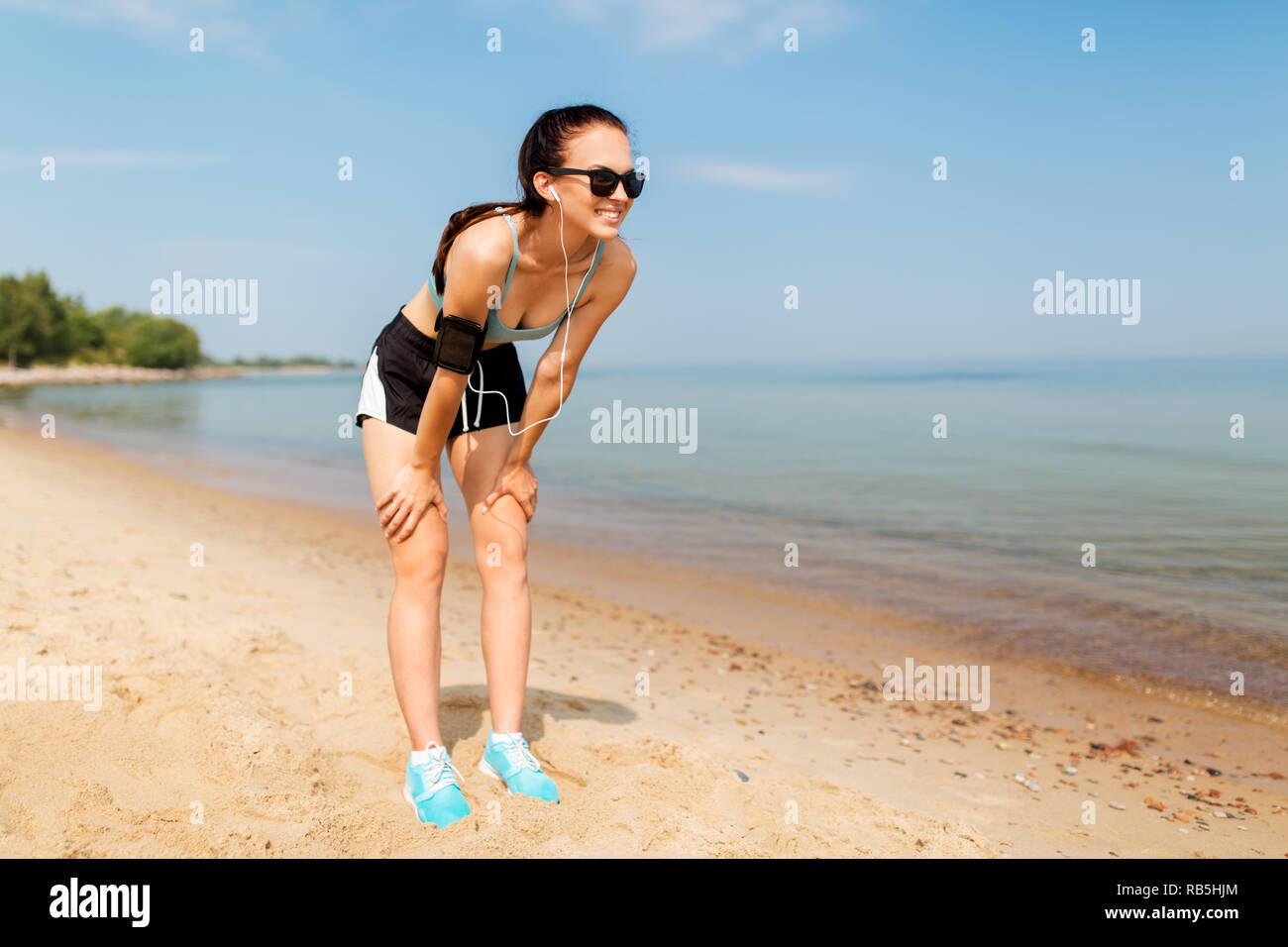 Femminile con gli auricolari e fascia per il braccio sulla spiaggia Immagini Stock