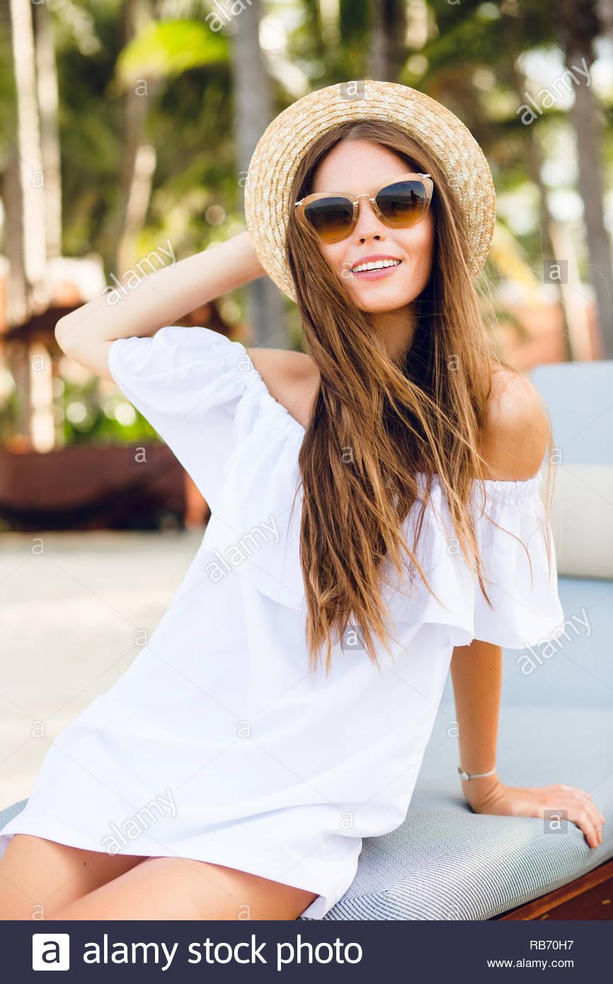 Ragazza carina in marrone occhiali da sole e cappello di paglia sorrisi  splendidamente. Indossa bianco 1e3b8fd4be71