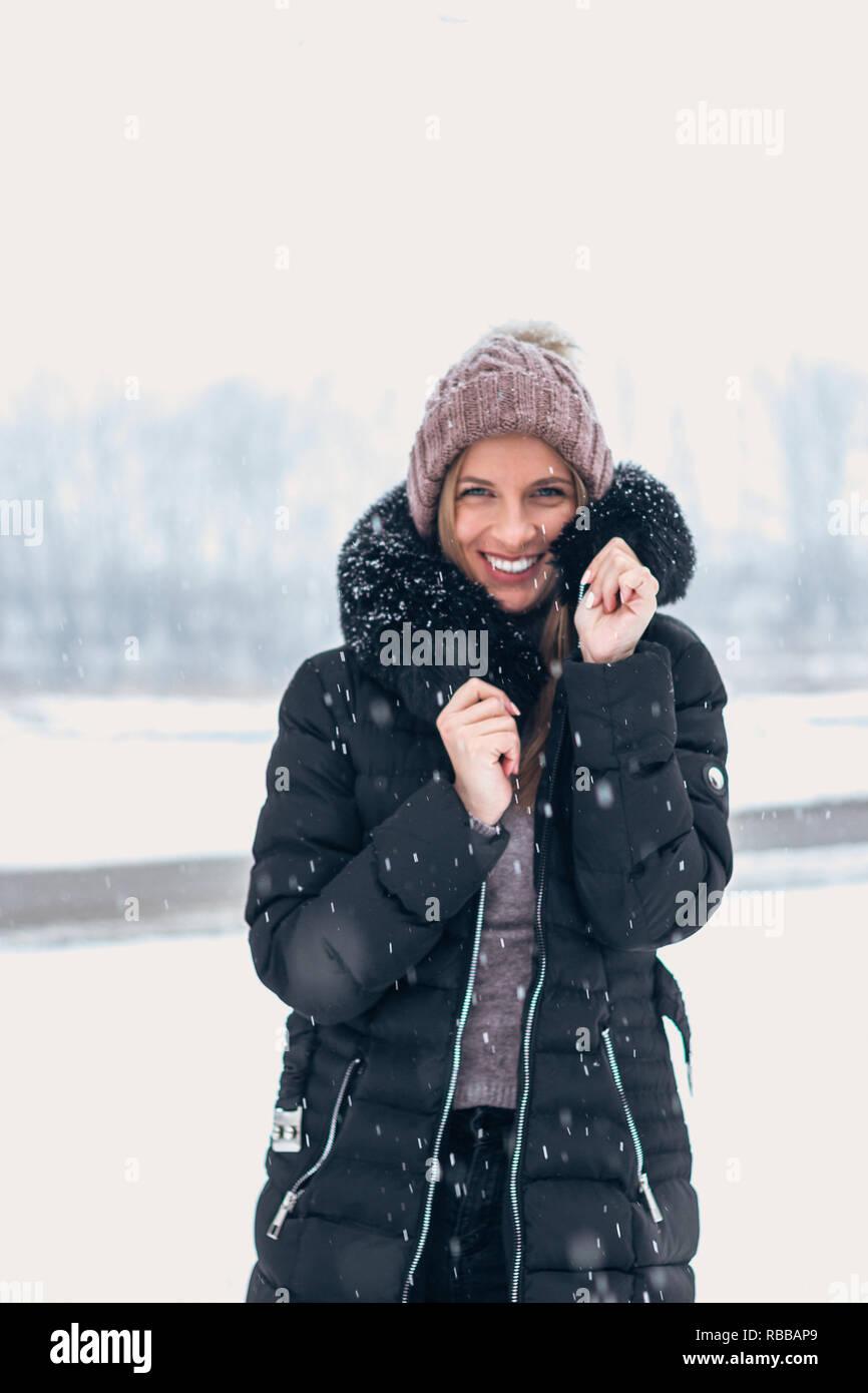 Donna sorridente in tempo freddo mentre la caduta della neve. Foto Stock