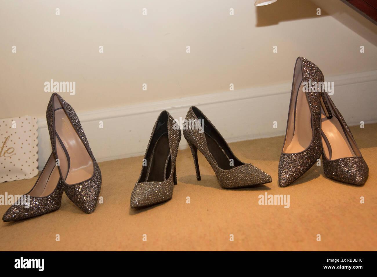 Le spose di scarpe con pattini bridesmaids allineati e in attesa di essere indossato su un giorno di nozze, nero e argento scintillanti scarpe nuziale Immagini Stock