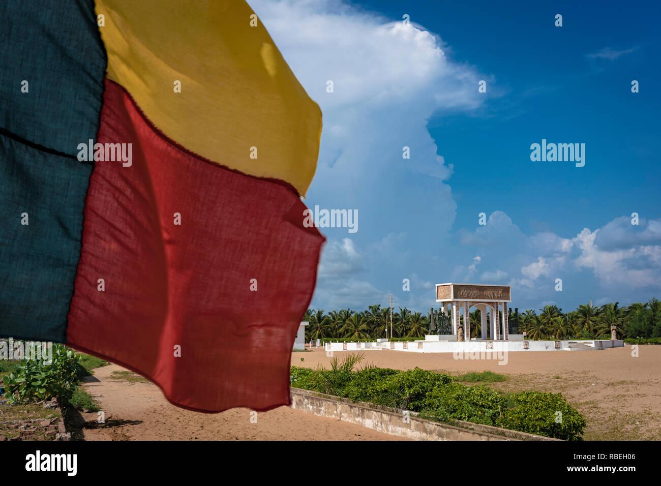 Il flag Beninese in primo piano con la porta di non ritorno (Porte du non retour) a Ouidah in background, un ex schiavi post in Benin. Foto Stock