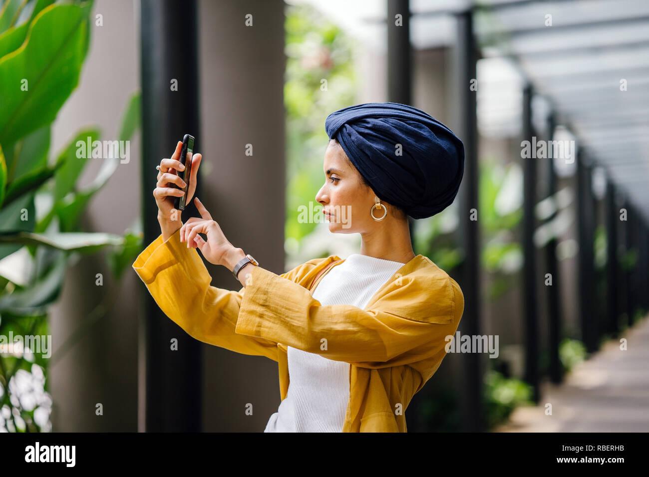 8d5e038b7335 Un giovane e attraente malay musulmana la donna in un elegante vestito  color pastello e un