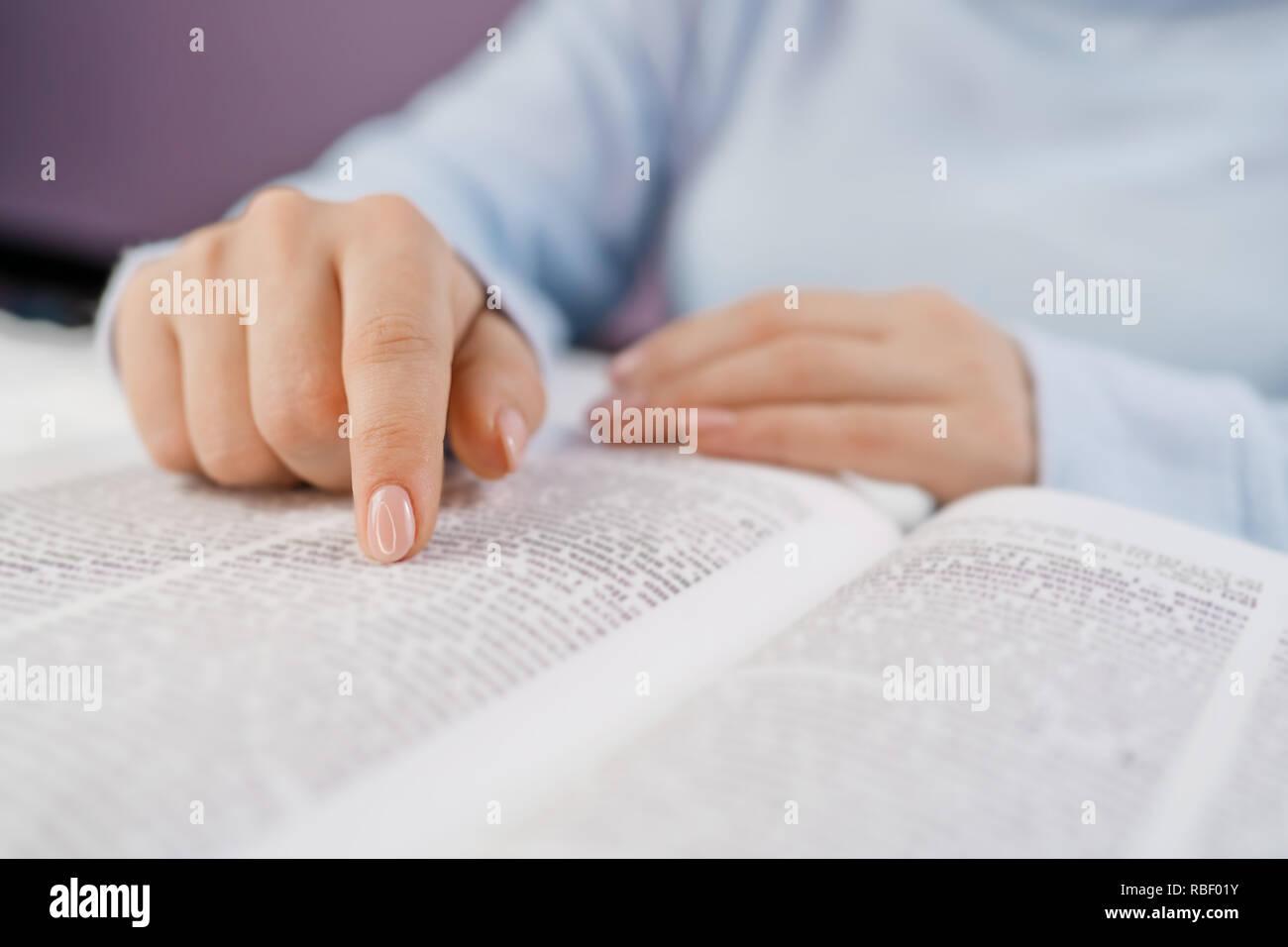 Studente nella biblioteca del college la preparazione per gli esami. Apprendimento, gratitudine, il concetto di religione. Irriconoscibile donna lettura big book - la Santa Bibbia e pregando. Christian studiare le scritture. Foto Stock