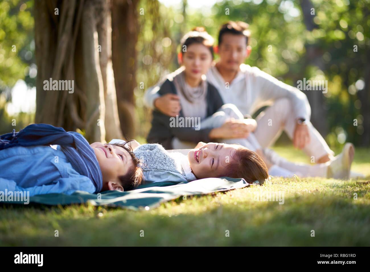 Due bambini asiatici piccolo ragazzo e ragazza divertirsi sdraiati sull'erba con i genitori seduti a guardare in background. Foto Stock