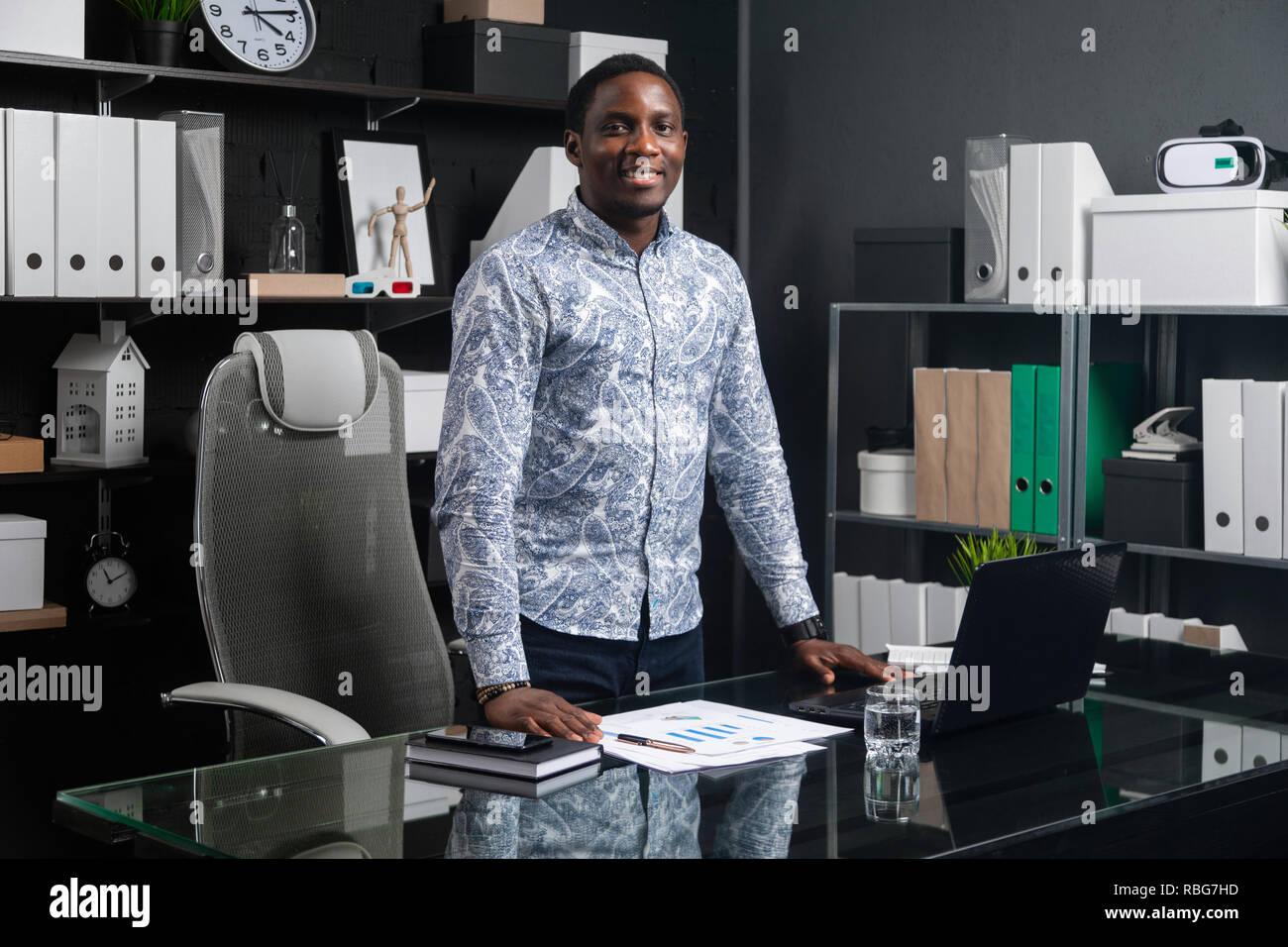 Ritratto di tre quarti lungo giovane imprenditore nero in piedi vicino alla scrivania in ufficio Immagini Stock