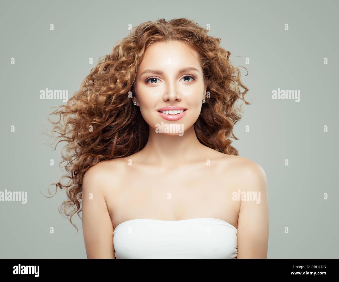 Giovane bella donna con sani lunghi capelli ricci. Ragazza sorridente su  sfondo grigio Immagini Stock 3c398c8dd42c