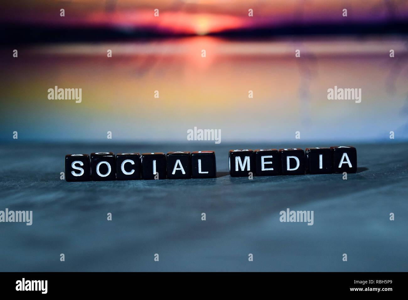 Social media su blocchi di legno. Croce immagine elaborata con sfondo bokeh di fondo Immagini Stock