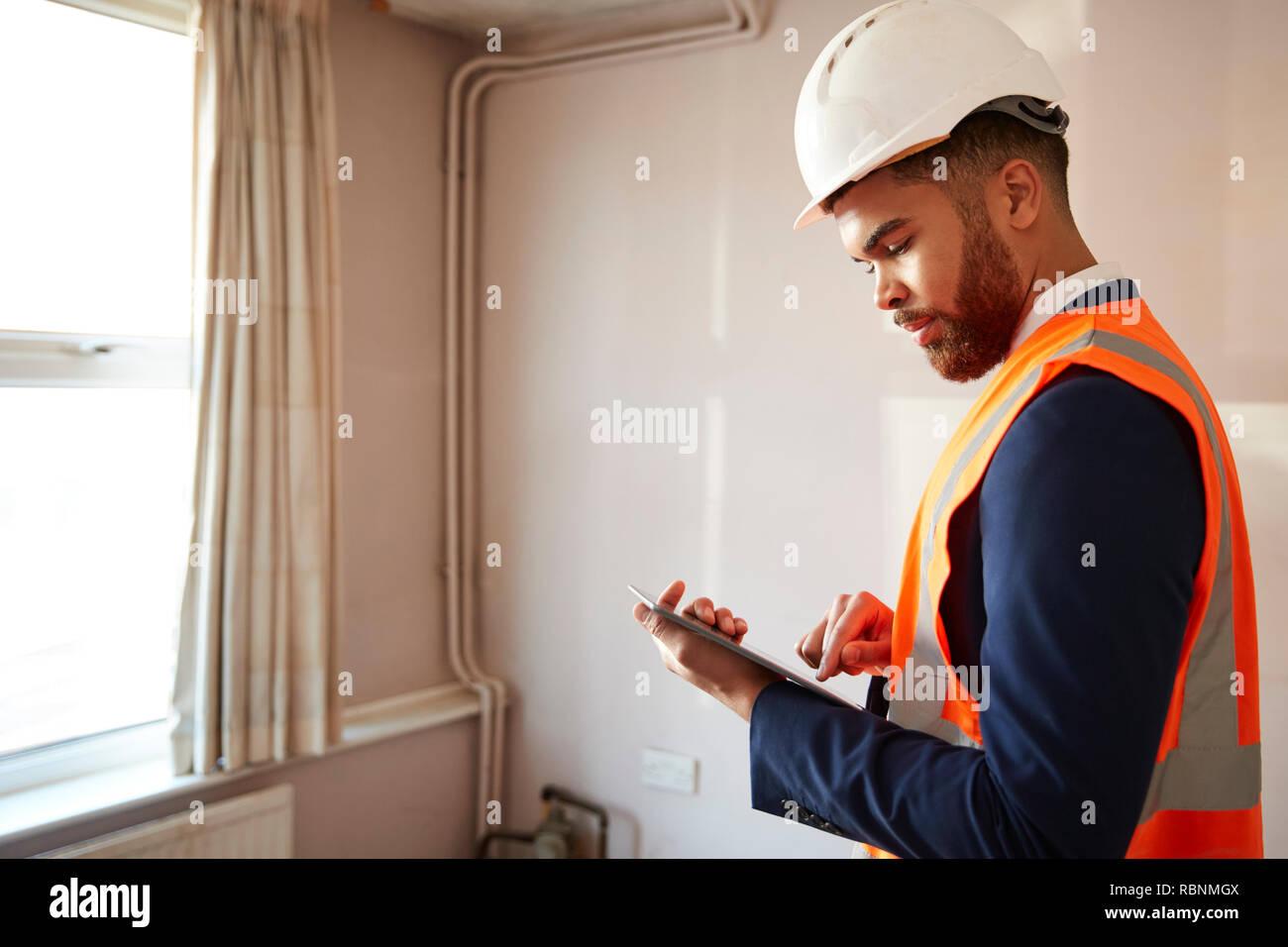 Geometra In elmetto e di alta visibilità giacca con tavoletta digitale effettuare ispezioni Casa Immagini Stock