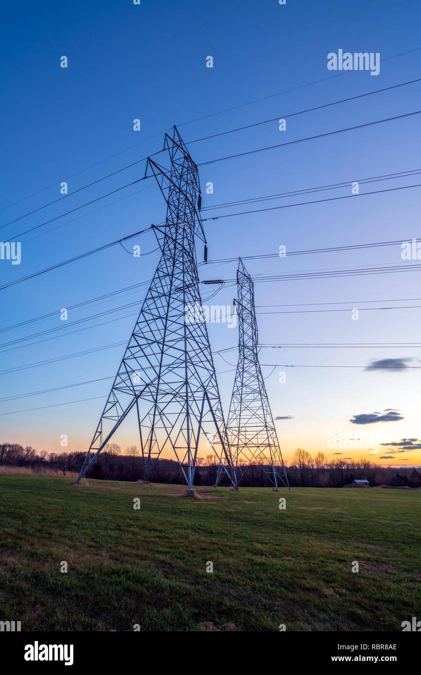 La distribuzione di energia elettrica le torri e i fili al crepuscolo Foto Stock