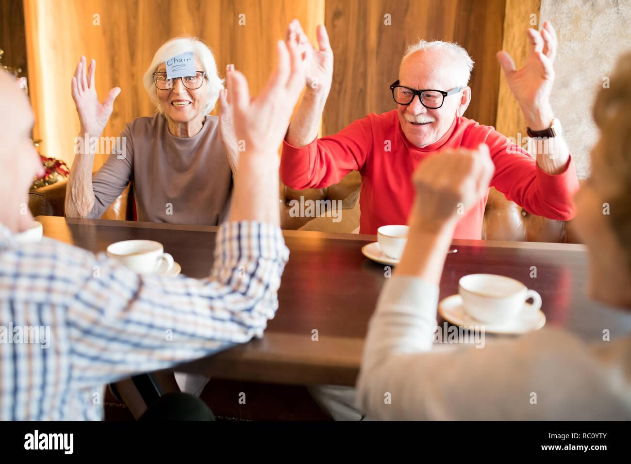 Emozionato senior amici giocando in cafe Foto Stock