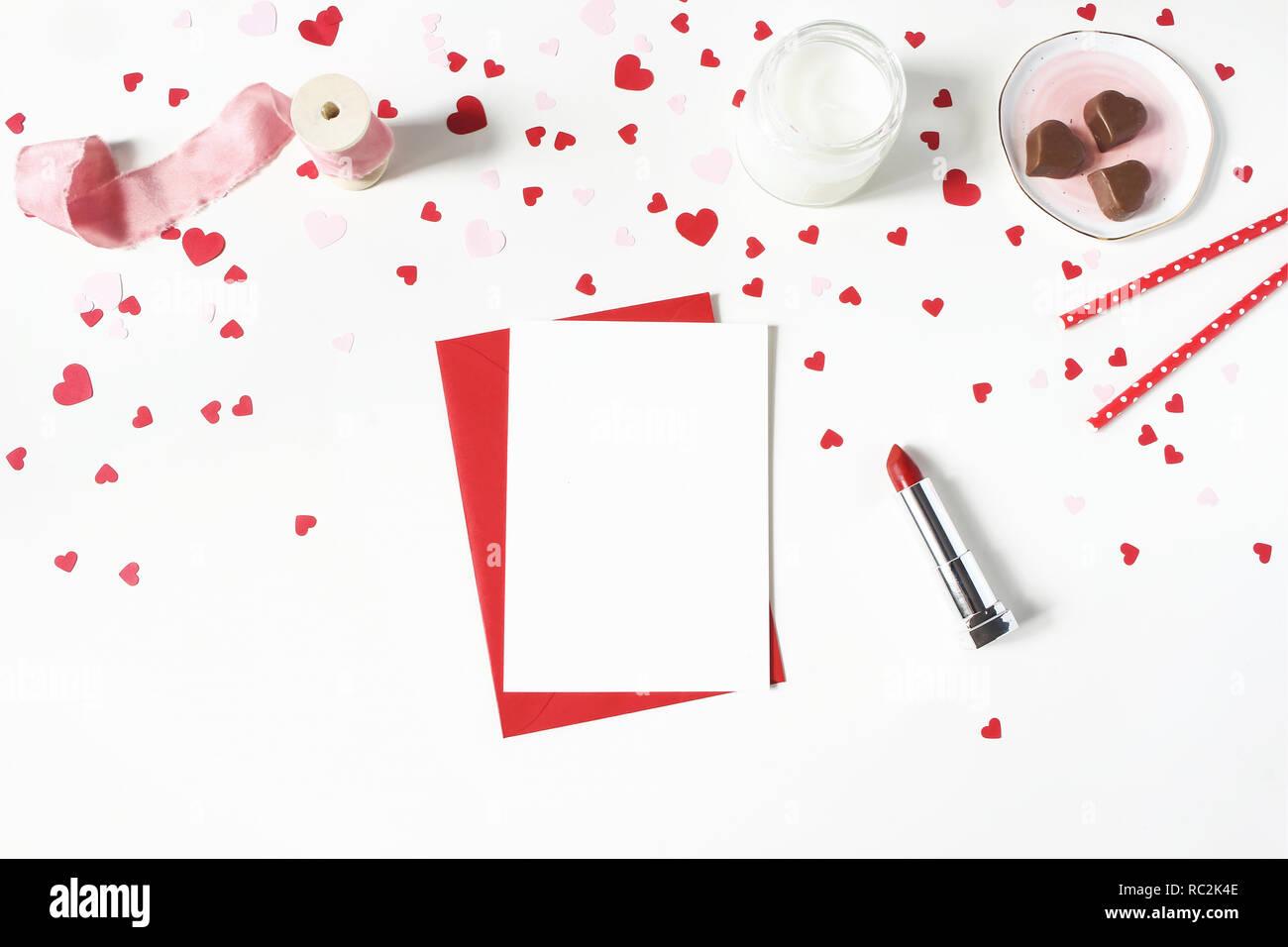 Il giorno di San Valentino, wedding still life scena. Candela, carta coriandoli, Cioccolato cuori, rossetto e bigliettino vuoto mockup sul tavolo bianco sullo sfondo. Il concetto di amore. Appartamento laico, vista dall'alto. Foto Stock