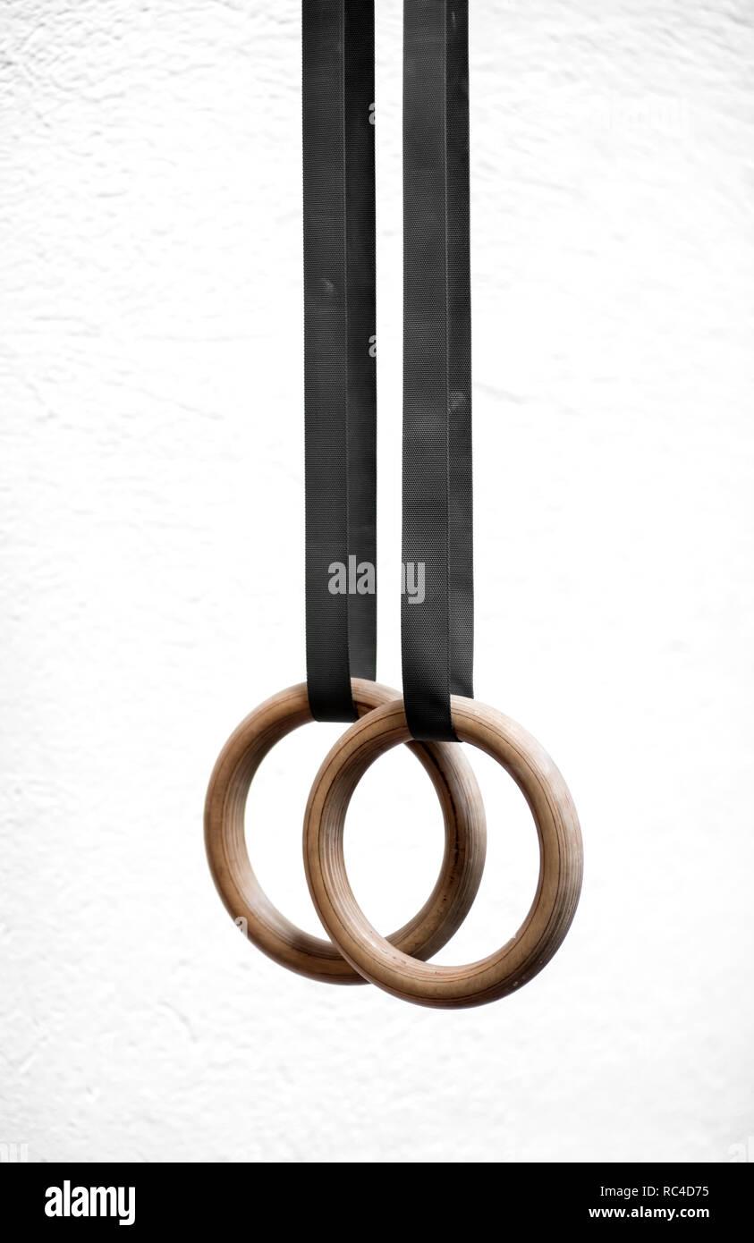 Coppia di sport in legno anelli costante per ginnastica, hang con calma su nero Cinturini in verticale close-up su sfondo bianco Immagini Stock