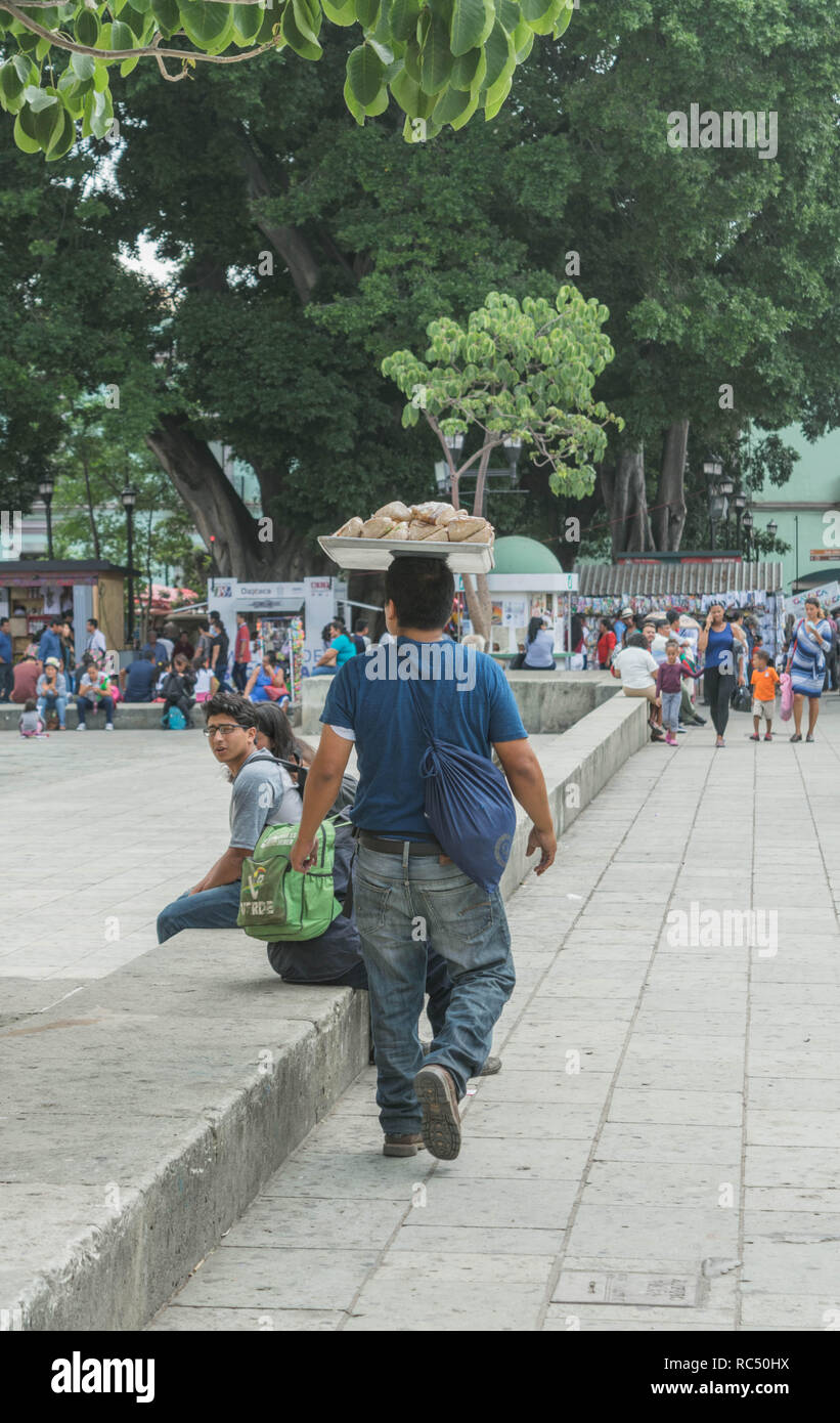 Uomo che cammina con un piatto di cibo sul suo capo, vicino dallo Zocalo, in Oaxaca, Messico Immagini Stock