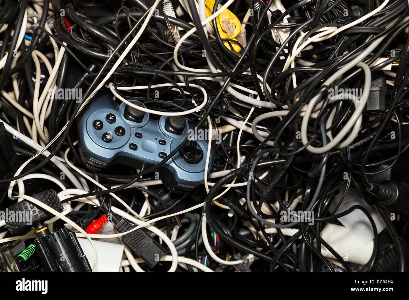 Close-up di un aggrovigliato mucchio di rottami di elettronica comprendente un gioco console controller in attesa per il riciclaggio Immagini Stock