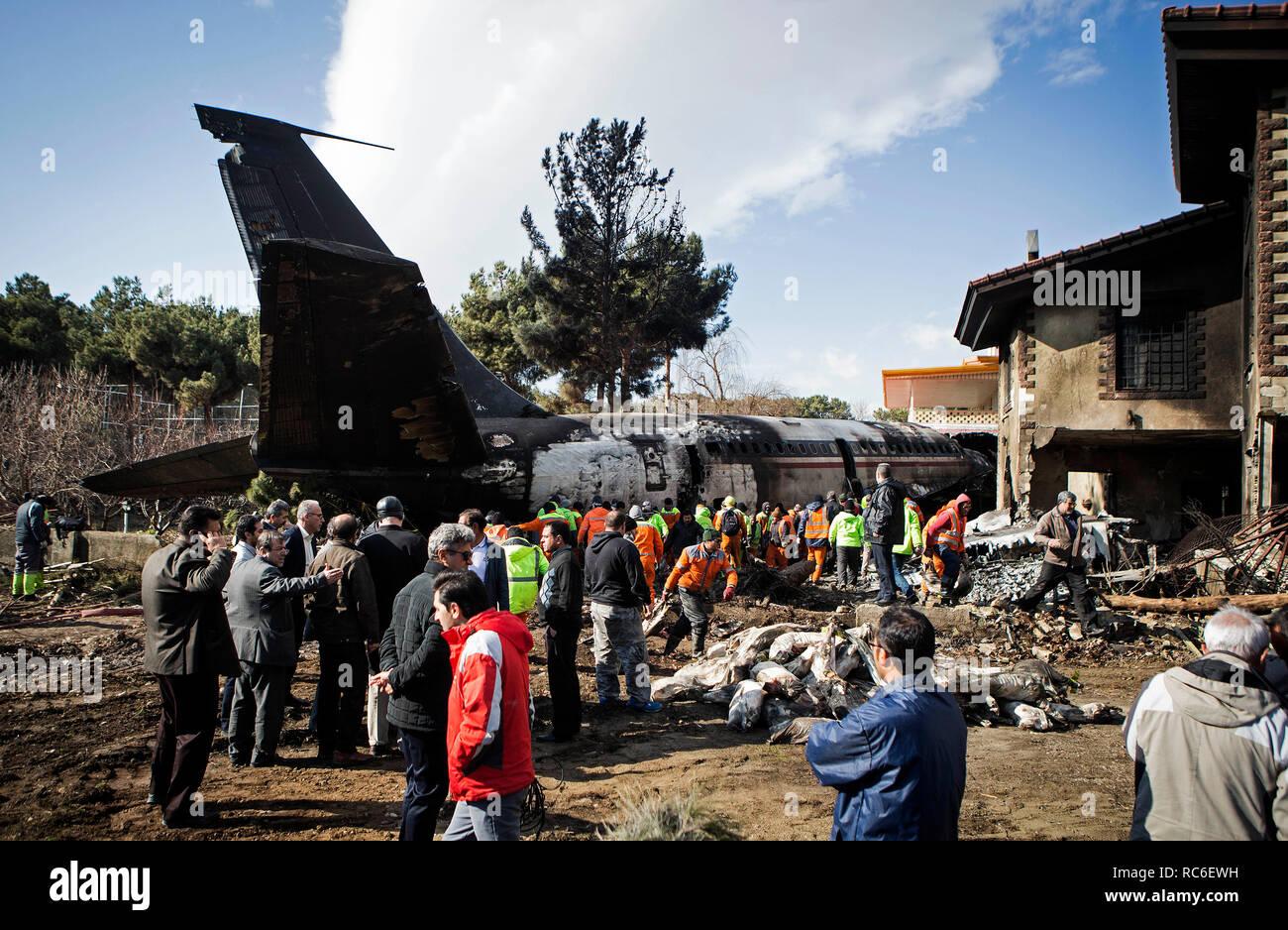 Karaj, Iran. Xiv gen, 2019. Soccorritori lavoro presso il sito del crash di un Boeing 707 piano in Karaj, Iran, 14 gennaio 2019. Almeno 15 persone sono state uccise il lunedì in crash. Credito: Ahmad Halabisaz/Xinhua/Alamy Live News Immagini Stock