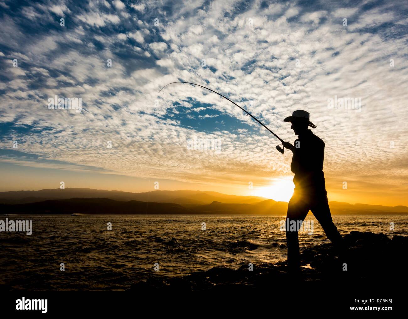 L'uomo della pesca in mare, la pesca sportiva al tramonto. Immagini Stock